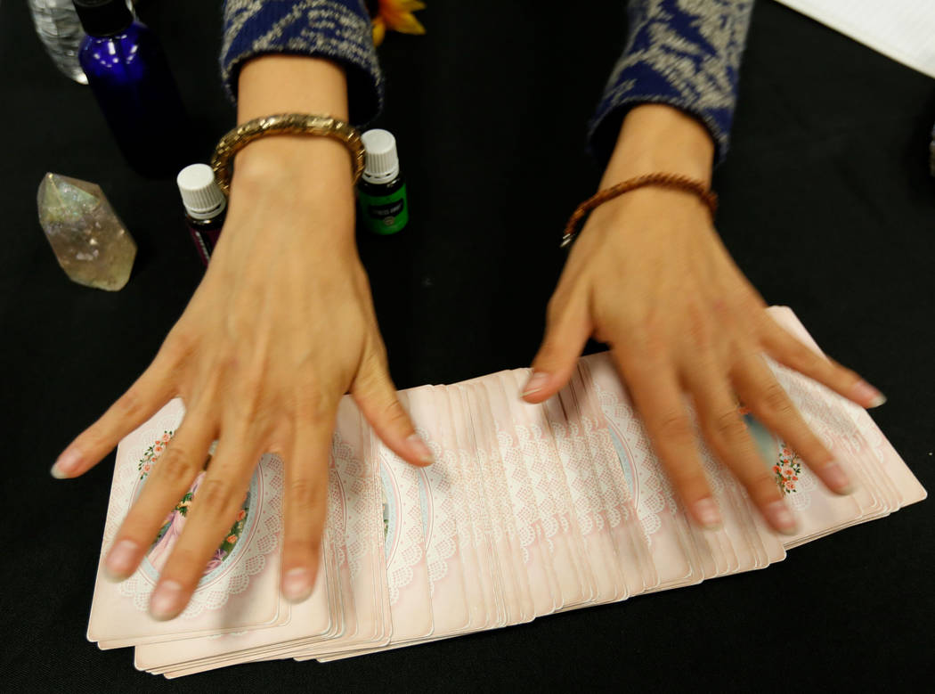 Local psychic Jennifer Pulcini shows her angel cards during Mystic Fair at Windmill Library in ...