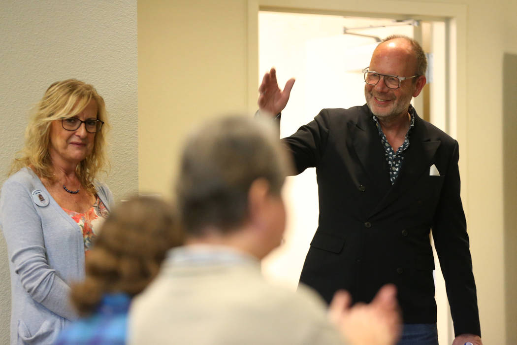 Stuart Holbrook, right, president of Theriault's, greets the crowd as Barbara Cennemo looks on, ...