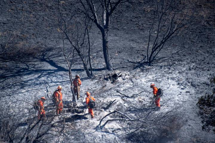 Firefighters put out hot spots in the Porter Ranch area of Los Angeles on Saturday, Oct. 12, 20 ...