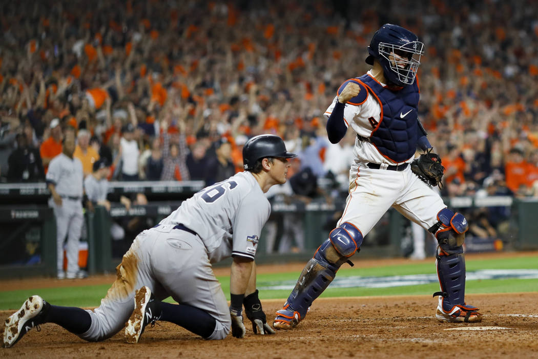 Houston Astros catcher Robinson Chirinos, right, celebrates after tagging out New York Yankees' ...