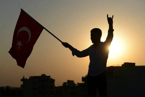 A Turkish youth celebrates with a national flag after news about Syrian town of Tal Abyad, in T ...