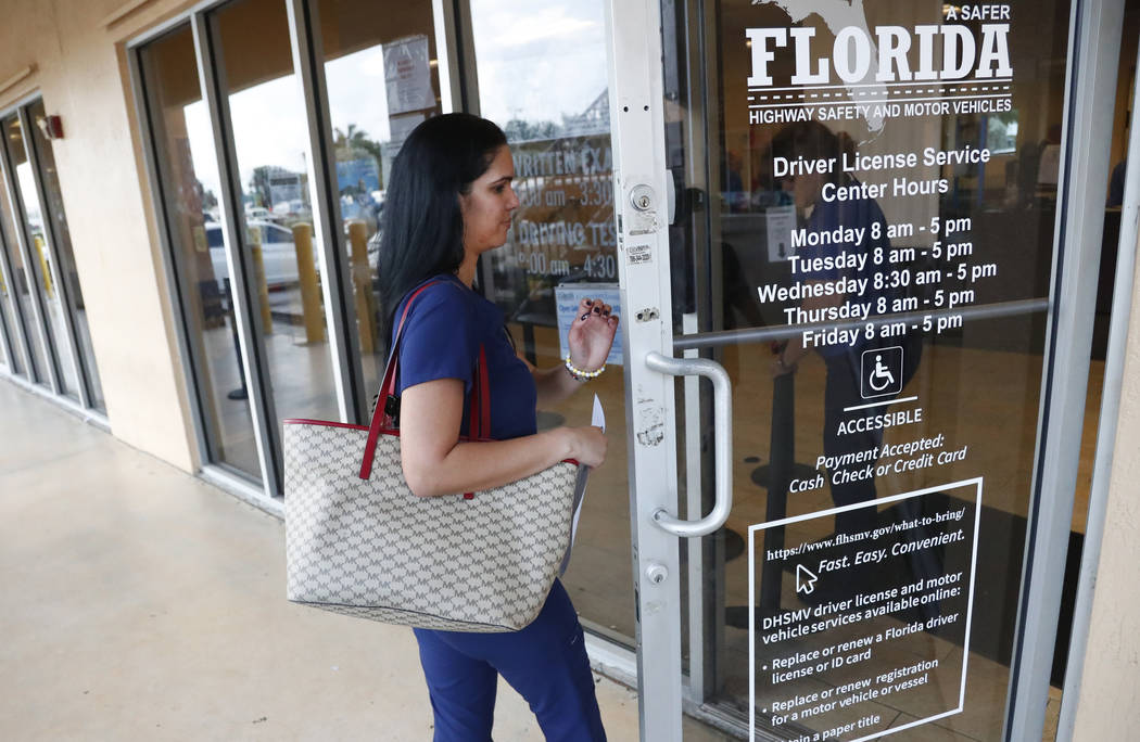 A woman enters a Florida Highway Safety and Motor Vehicles drivers license service center on Tu ...