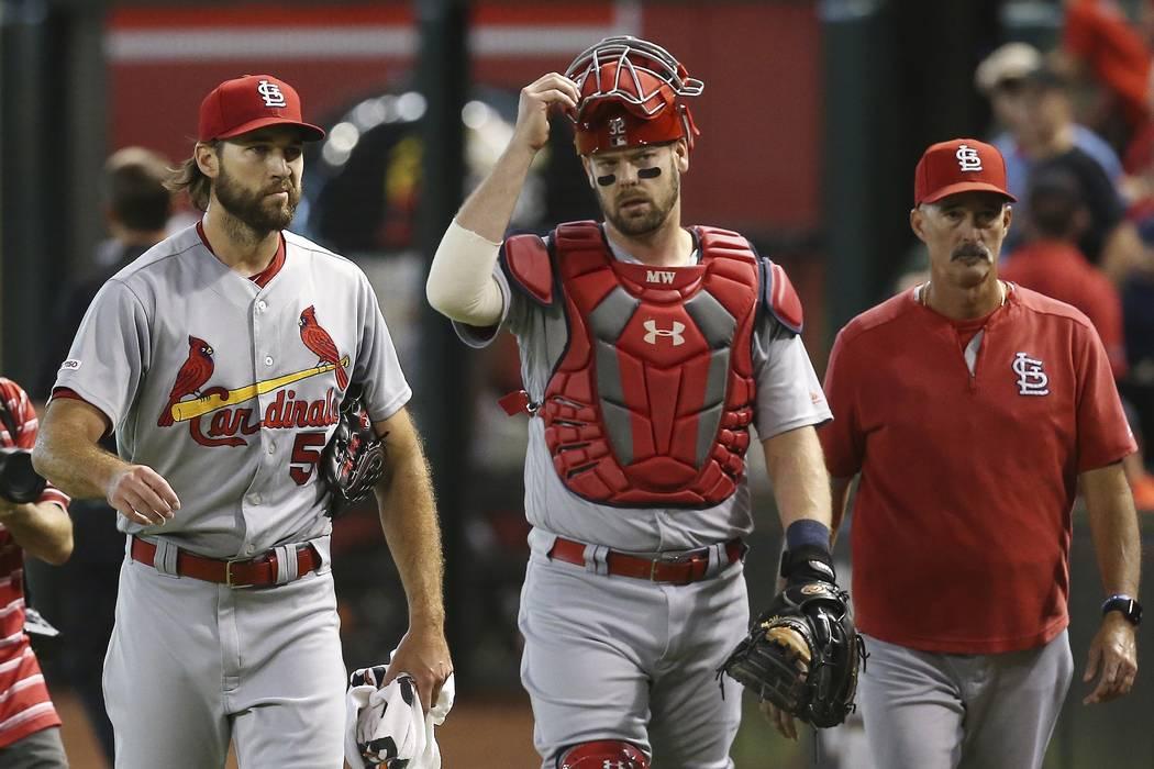 St. Louis Cardinals starting pitcher Michael Wacha, left, catcher Matt Wieters, middle, and pit ...