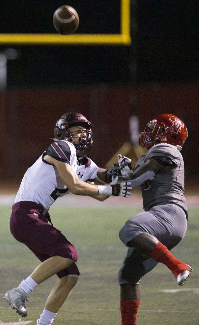 Faith Lutheran senior wide receiver Riley Schwartz (2) fights for a deflected pass with Arbor V ...