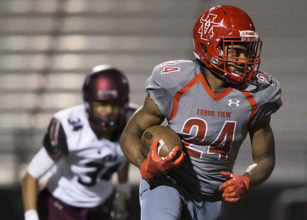 Arbor View senior running back Daniel Mitchell (24) cuts up field past Faith Lutheran sophomore ...