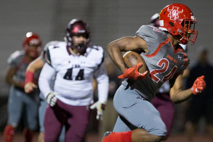 Arbor View senior running back Daniel Mitchell (24) breaks a big run past Faith Lutheran junior ...
