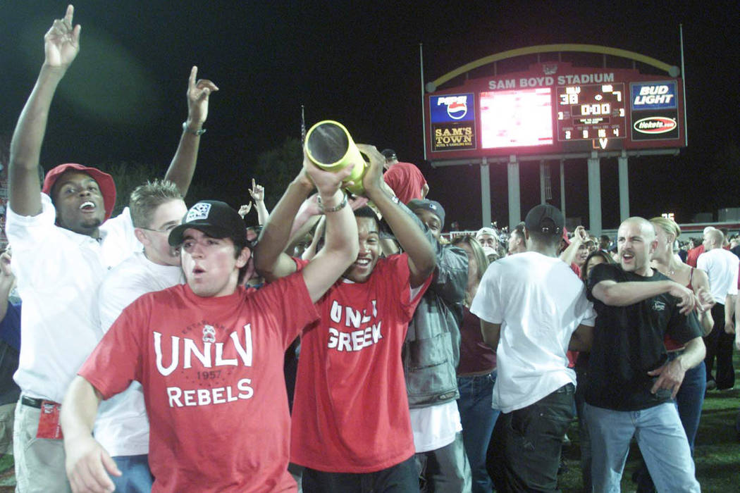 Sports; 10-07-00, UNLV football fans carry a piece of the goal post after the Rebels beat UNR. ...