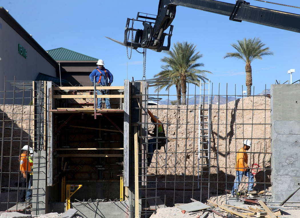 Workers build a retaining wall for a new Calida Group apartment complex at 8791 Alta Drive in L ...