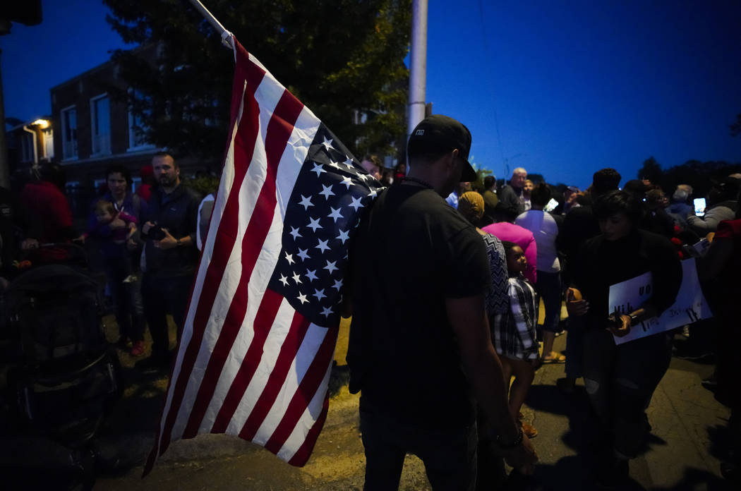 A large crowd of protesters, including a man carrying an upside-down American flag, gather outs ...