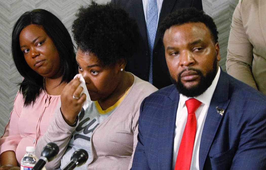 Amber Carr, center, wipes a tear as her sister, Ashley Carr, left, and attorney Lee Merritt, ri ...