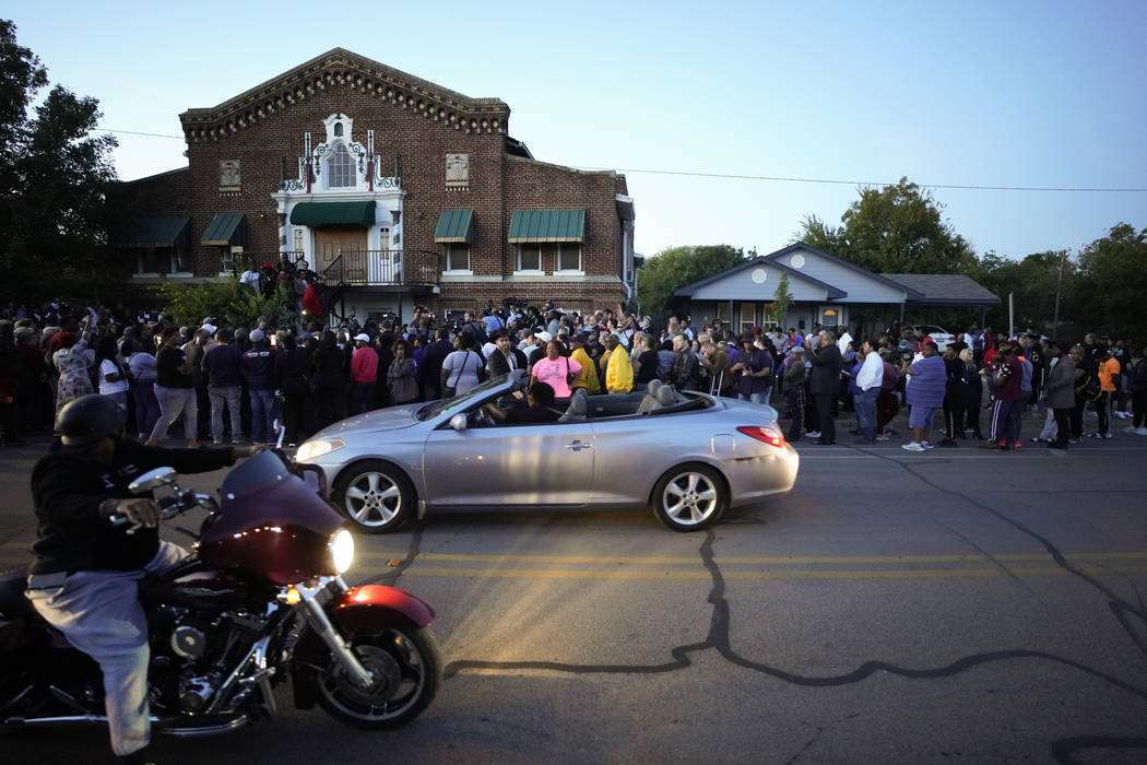 A large crowd of protesters gather outside the house, right, where Atatiana Jefferson was shot ...