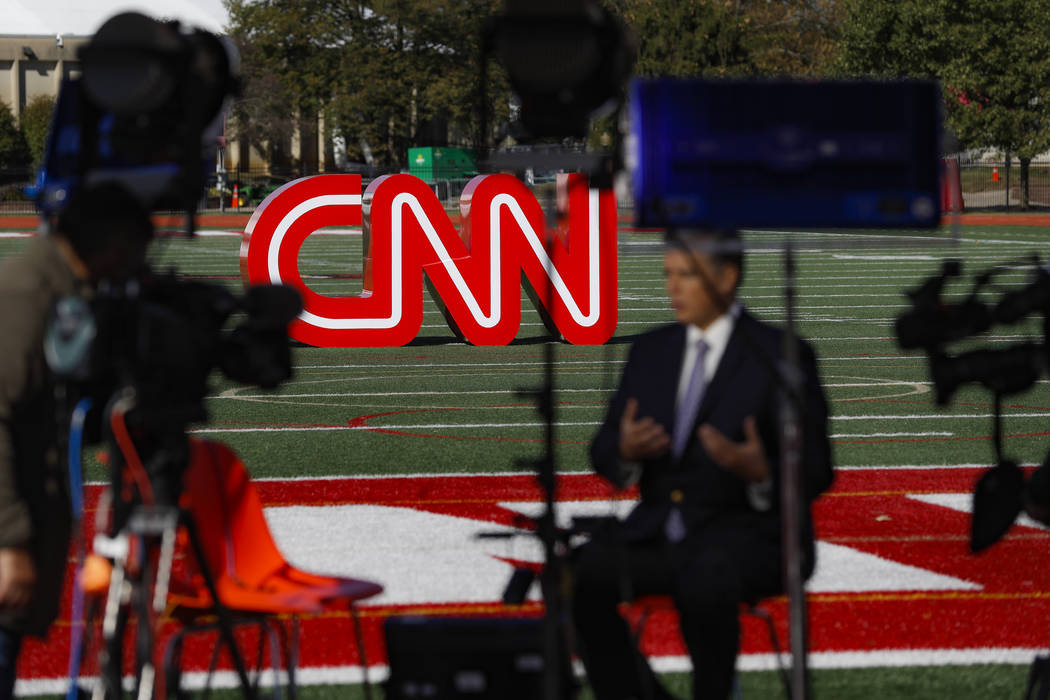 A journalist records video near a CNN sign on an athletic field outside the Clements Recreation ...