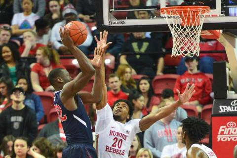 Fresno State Bulldogs forward Nate Grimes (32) takes a shot over UNLV Rebels forward Nick Blair ...