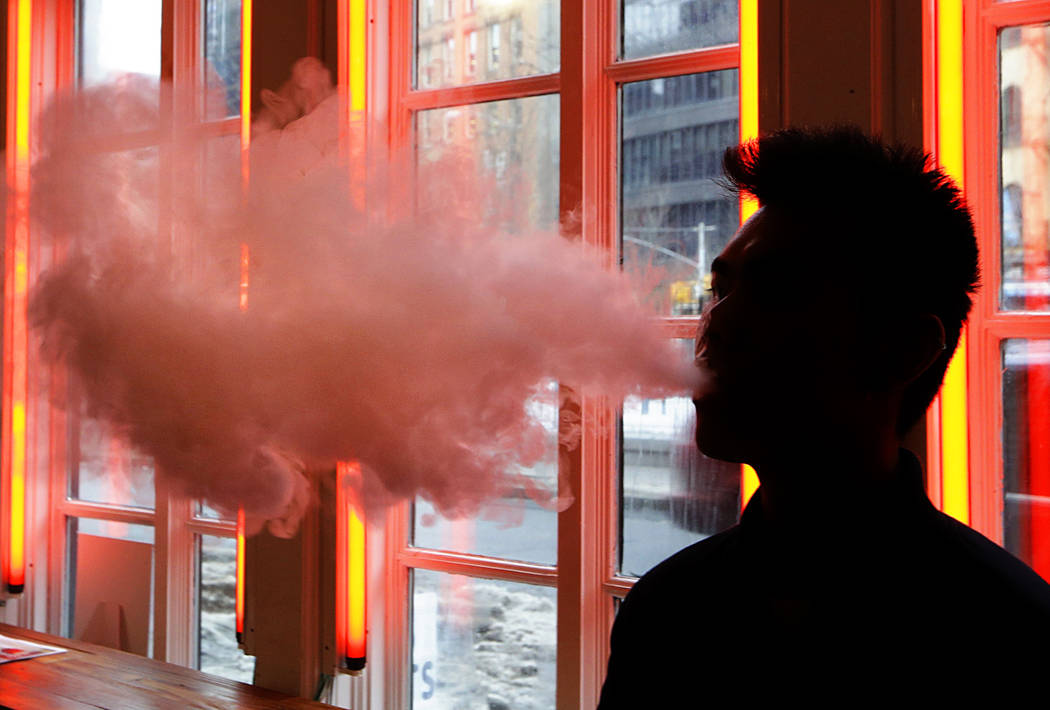 In a Feb. 20, 2014, file photo, a patron exhales vapor from an e-cigarette at a store in New Yo ...