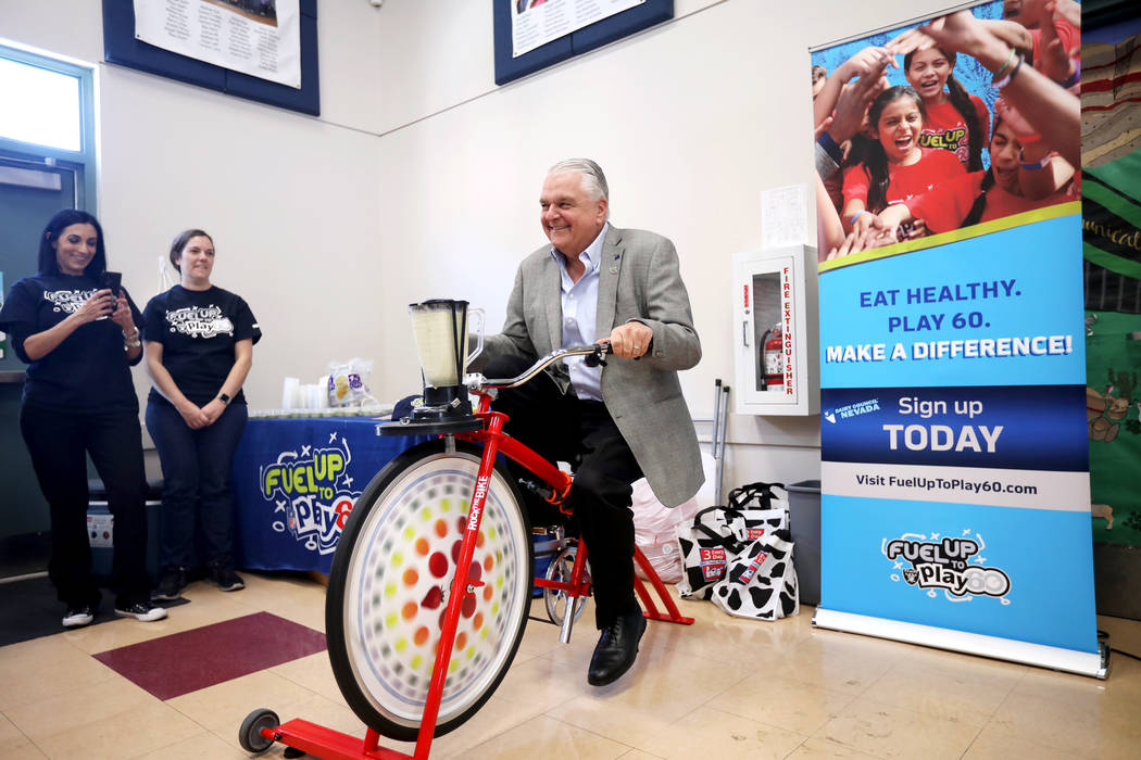 Gov. Steve Sisolak peddles a bike that powers a blender to make a smoothie at Staton Elementary ...