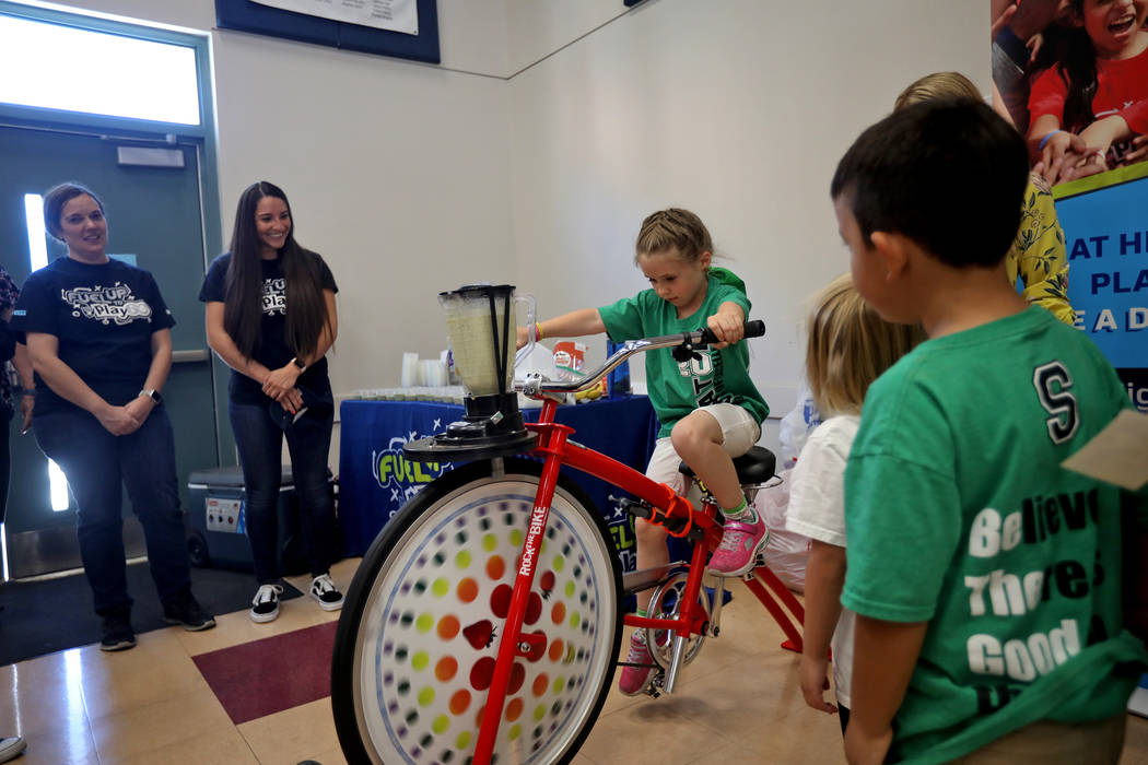 Isabella Duren, 5, peddles a bike that powers a blender to make a smoothie at Staton Elementary ...
