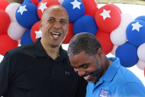 Democratic presidential candidate Sen. Cory Booker, D-N.J., left, shares a laugh after being in ...