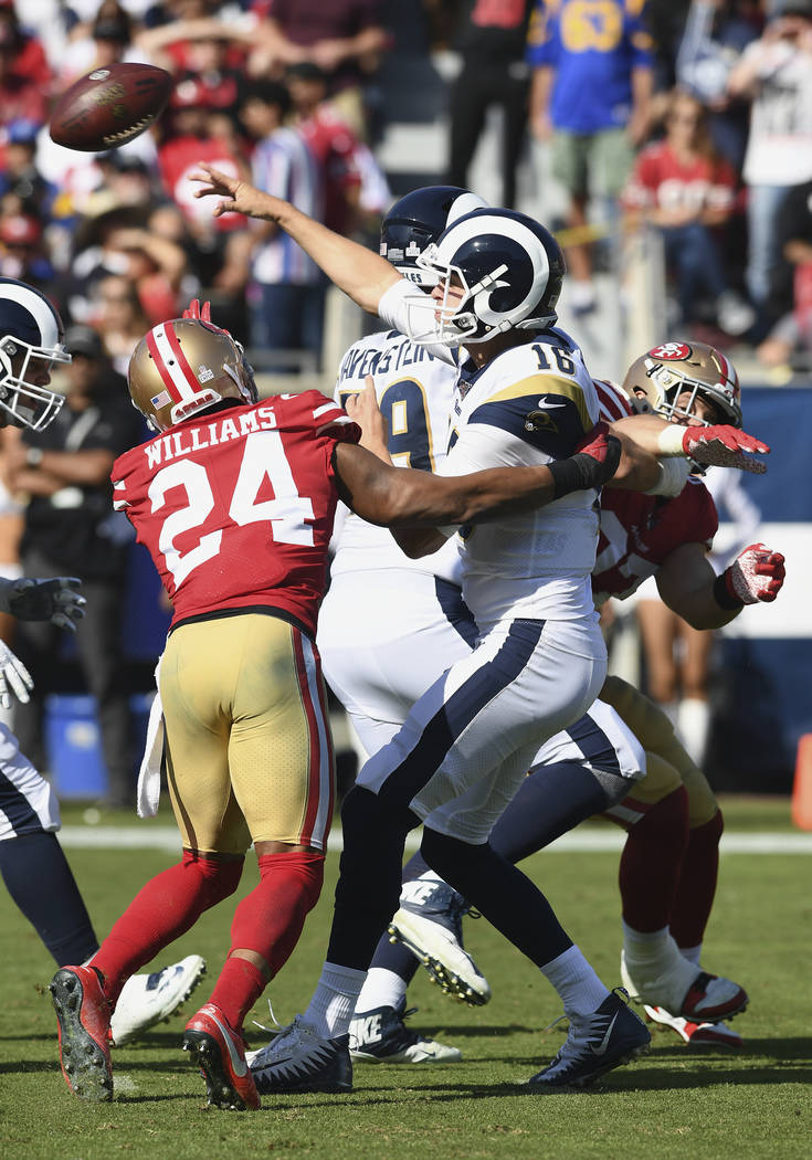 Los Angeles Rams quarterback Jared Goff (16) passes the ball under pressure during an NFL footb ...