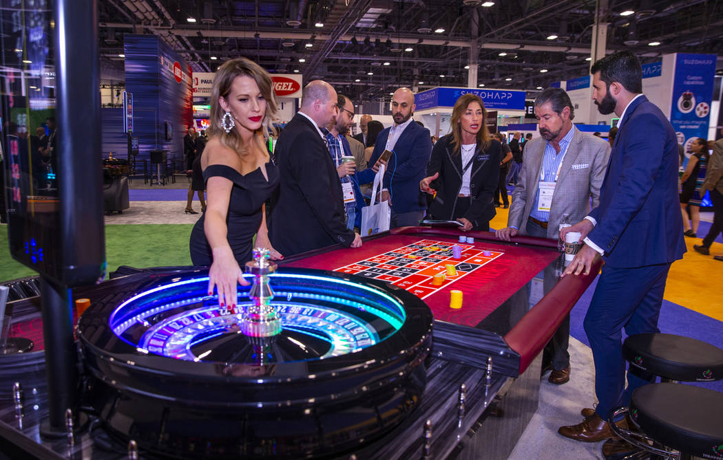 Attendees confer over a roulette table on display in the TCSJOHNHUXLEY exhibition space during ...