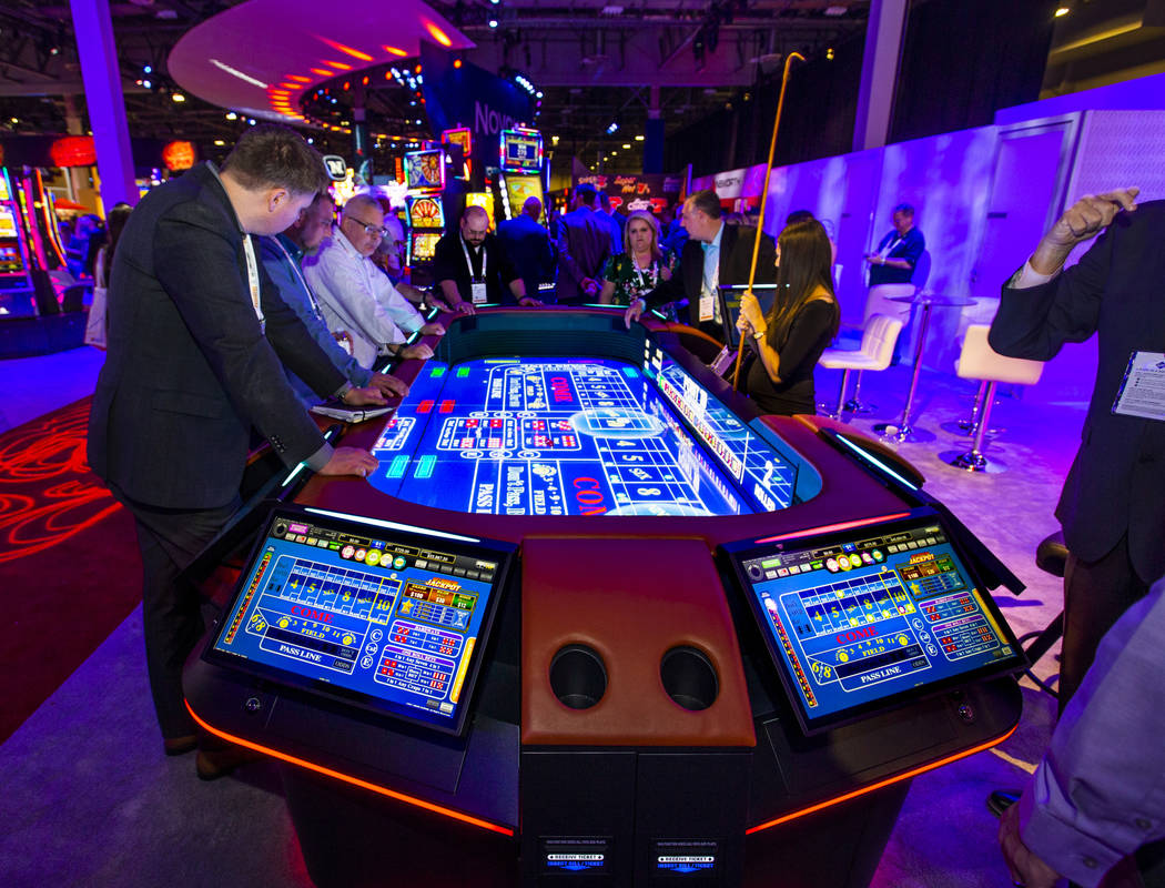 Attendees play on a new digital craps table from Aruze Gaming during the Global Gaming Expo 201 ...