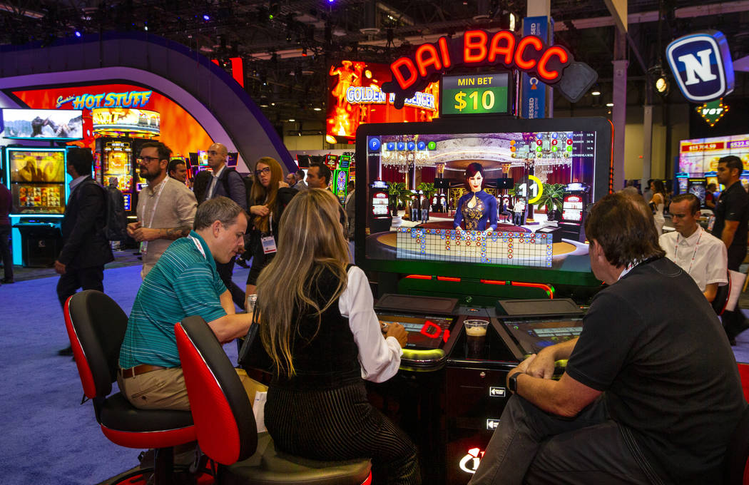 Attendees play the new Dai Bacc automated electronic table game by Interblock during the Global ...