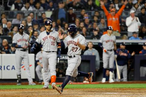 Houston Astros' Jose Altuve celebrates after scoring on a wild pitch during the seventh inning ...