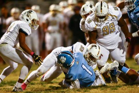 Faith Lutheran's Leonardo Mendoza (33) stops Centennial's Jordan Smith (1) during the second ha ...