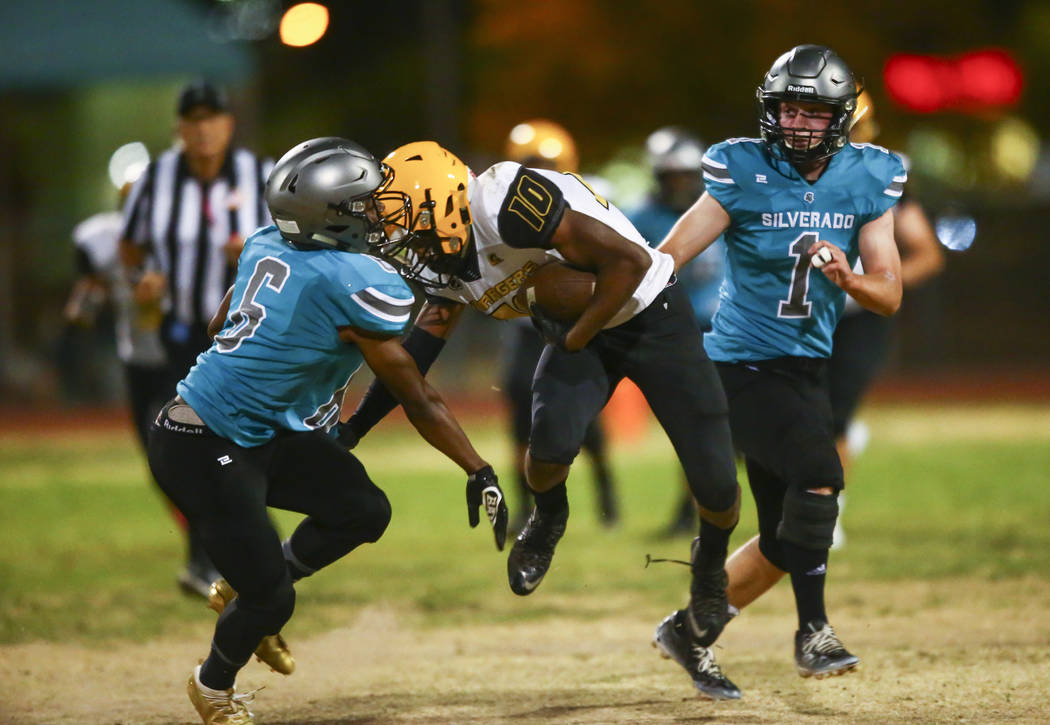 Clark's Dillan Lavender (10) gets stopped by Silverado's John Agounke (6) and Gregory Hunt (1) ...
