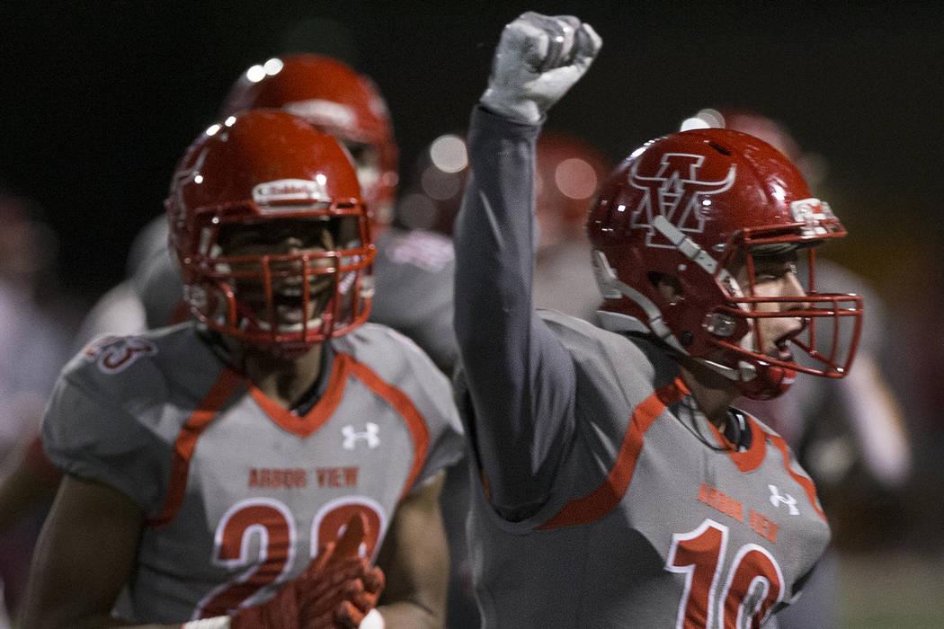 Arbor View senior defensive back Nolan Weir (19) celebrates with teammates after a big defensiv ...