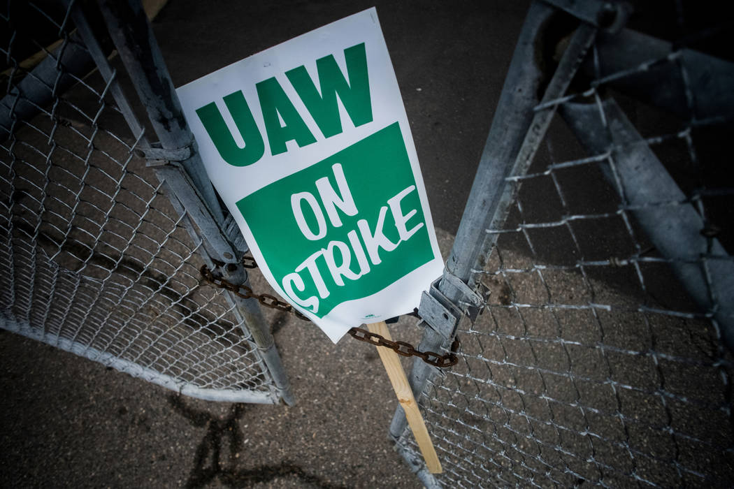A Sept. 16, 2019, file photo, shows a United Auto Workers strike sign resting between the chain ...
