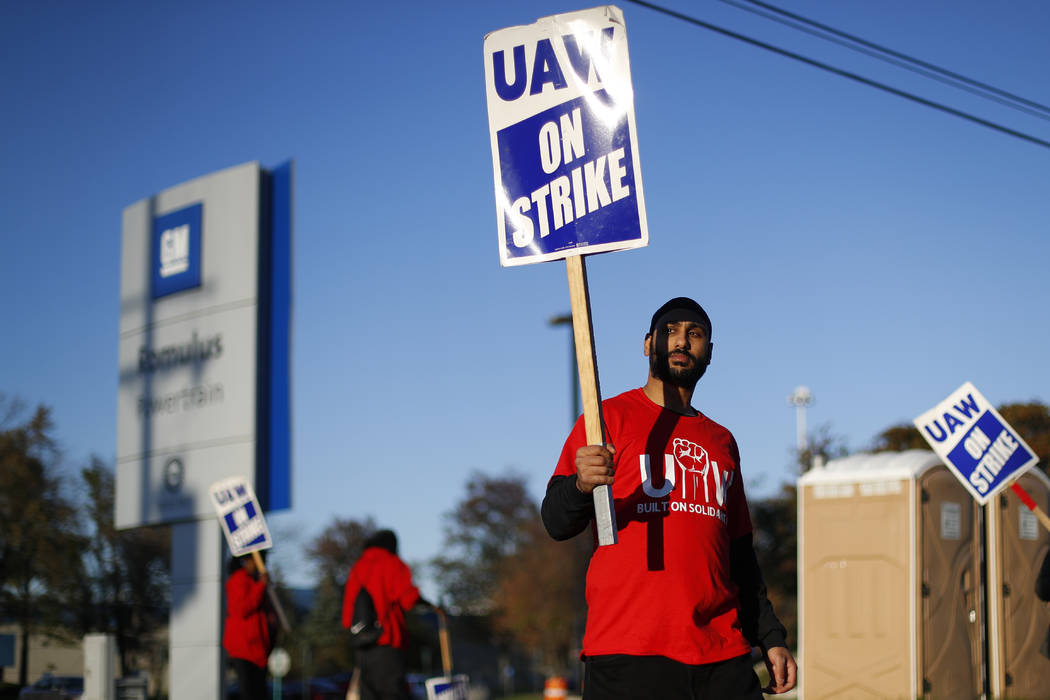 An Oct. 9, 2019, file photo a member of the United Auto Workers walks the picket line at the Ge ...