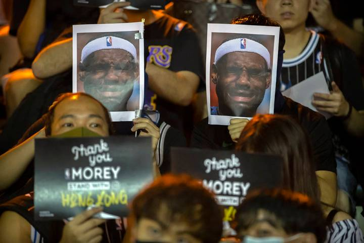 Demonstrators hold up photos of LeBron James grimacing during a rally at the Southorn Playgroun ...