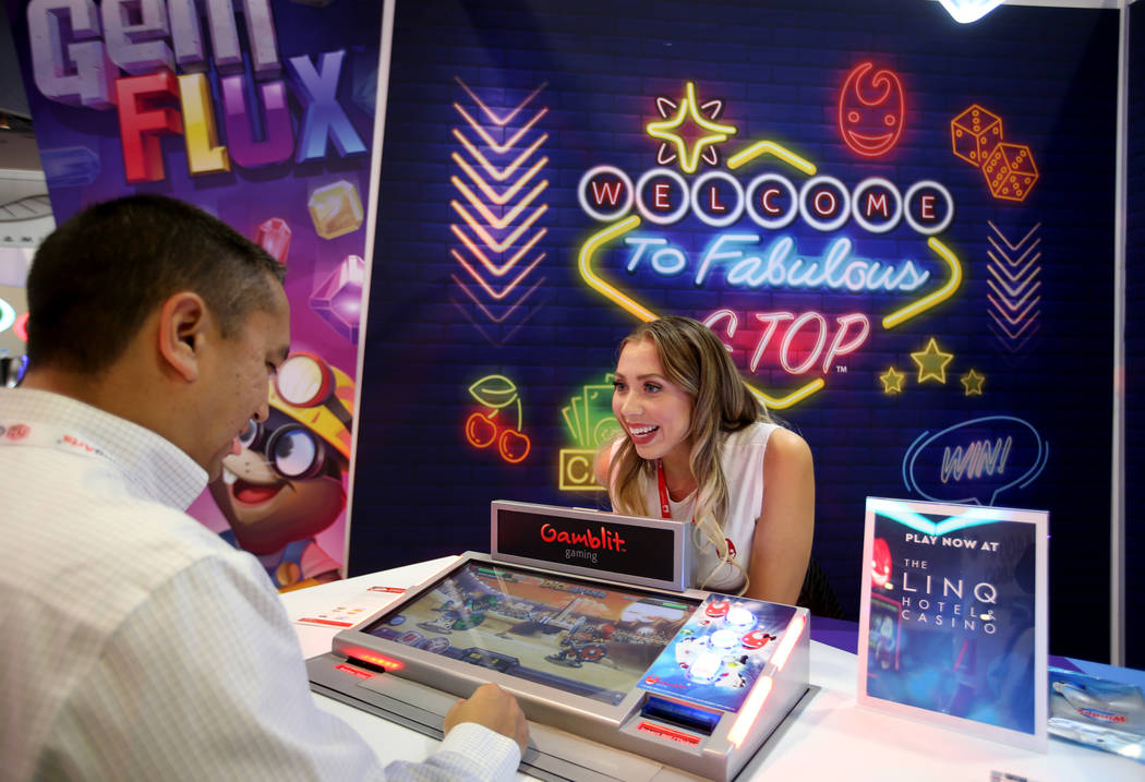 Alexia Bustios of Las Vegas shows Jason Oloriz of Las Vegas how to play the Dice Arena game at ...
