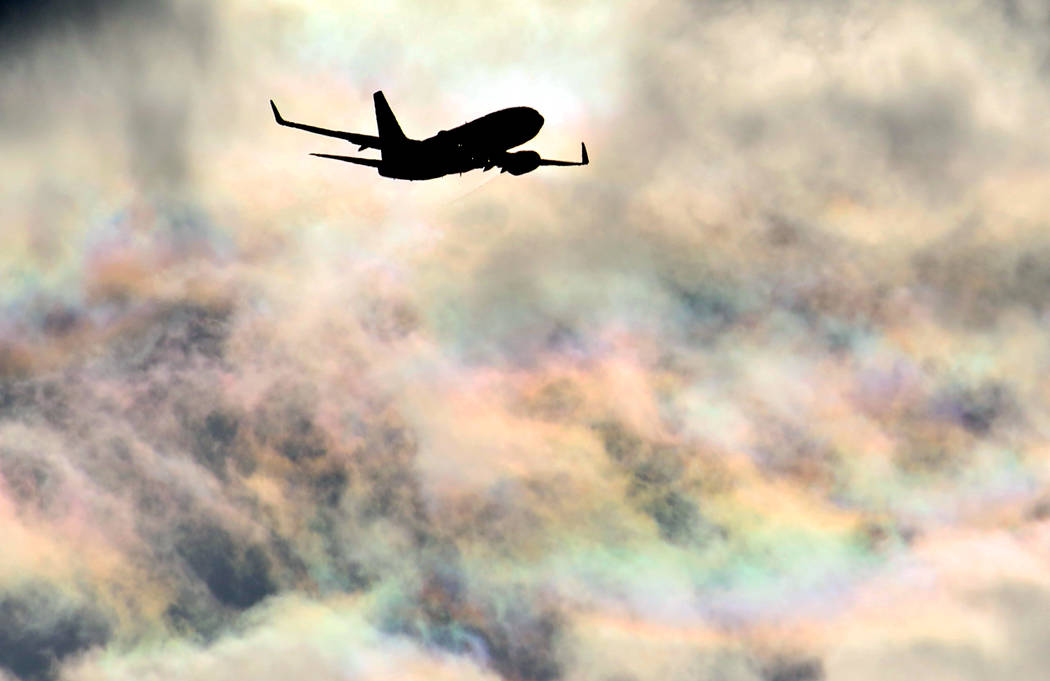 A Southwest Airlines plane flies under rainbow sky as it approaches McCarran International Airp ...