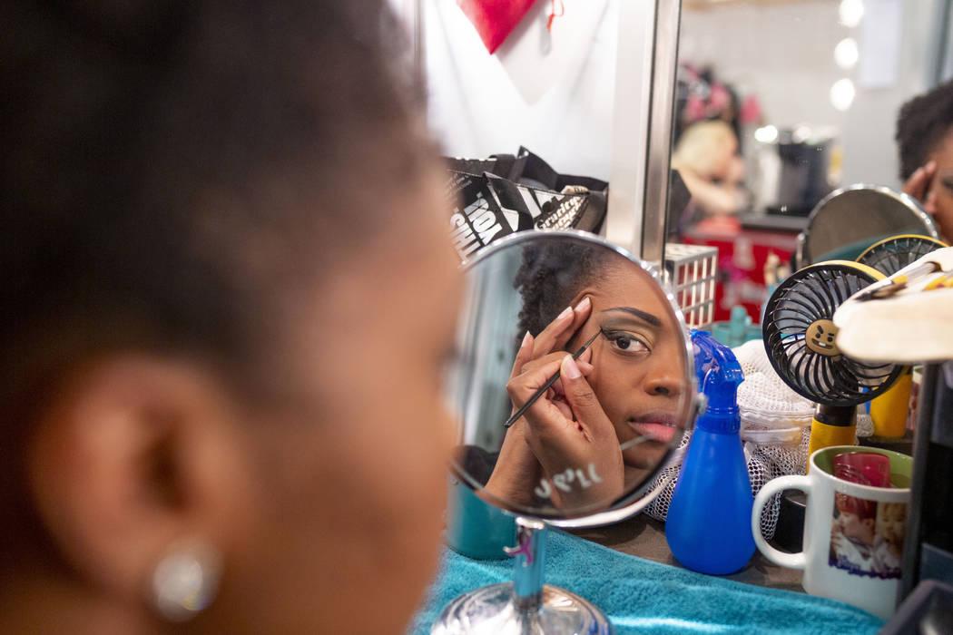 """""""Vegas! The Show"""" dancer Lauren Clark applies her makeup in the dressing room before ..."""