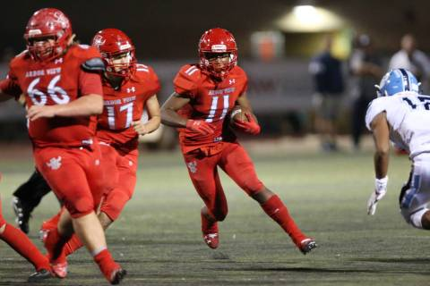 Arbor View's Jaedyn Jackson (11) runs the ball with Kyle Holmes (17) and Gavin Fleming (66) blo ...