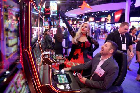 Joyce Jones of Las Vegas shows Maksym Maslii, of Digicode of Plano, Texas, how to play Jackpot ...