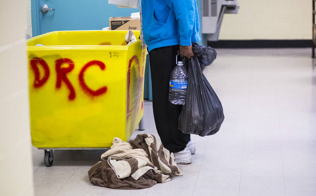 Patrons of The Salvation Army homeless shelter grab supplies near downtown Las Vegas on Tuesday ...