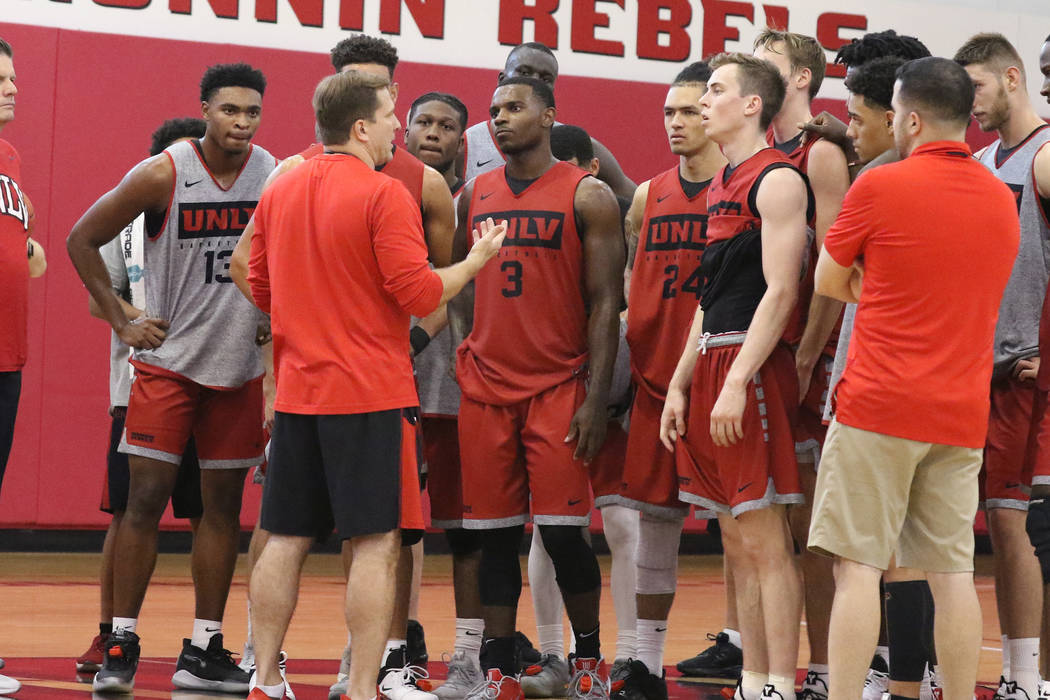 UNLV Rebels head coach T.J. Otzelberger, center, talks to his players after team's first basket ...