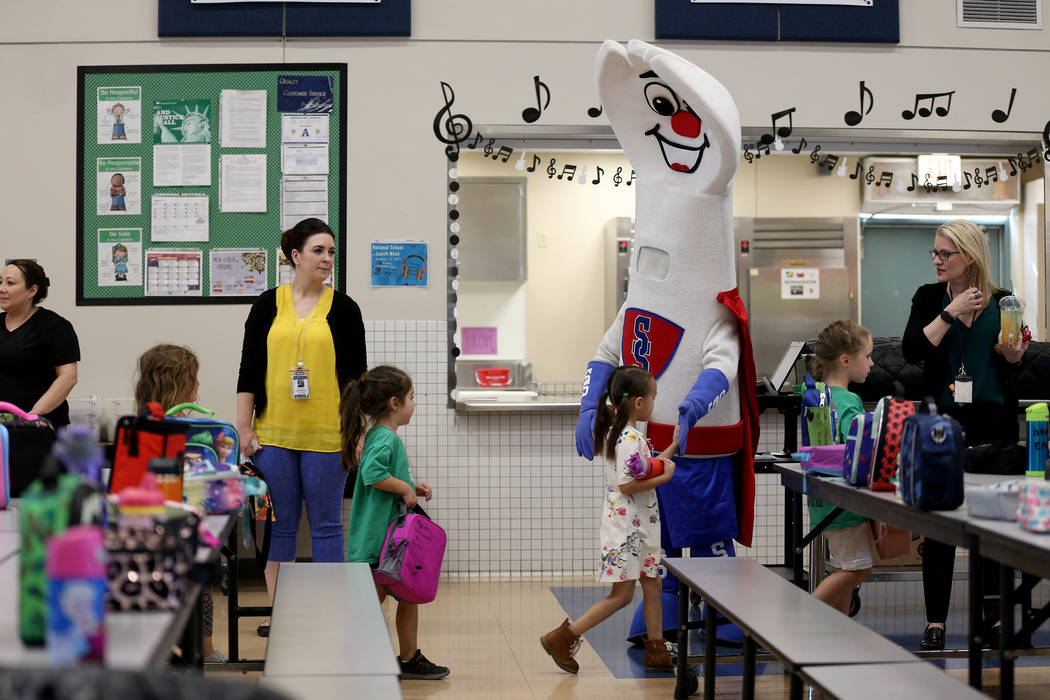 Clark County School District food services mascot Sporky high-fives students at Staton Elementa ...