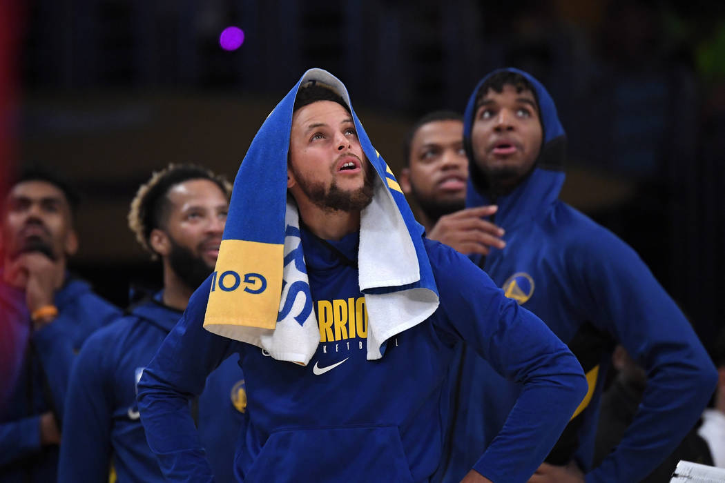 Golden State Warriors guard Stephen Curry looks at a replay along with teammates during the sec ...