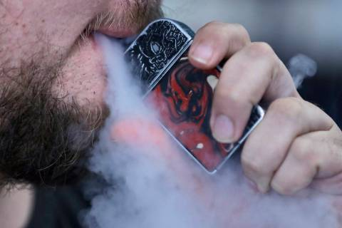 FILE - In this Friday, Oct. 4, 2019 photo, a man using an electronic cigarette exhales in Mayfi ...