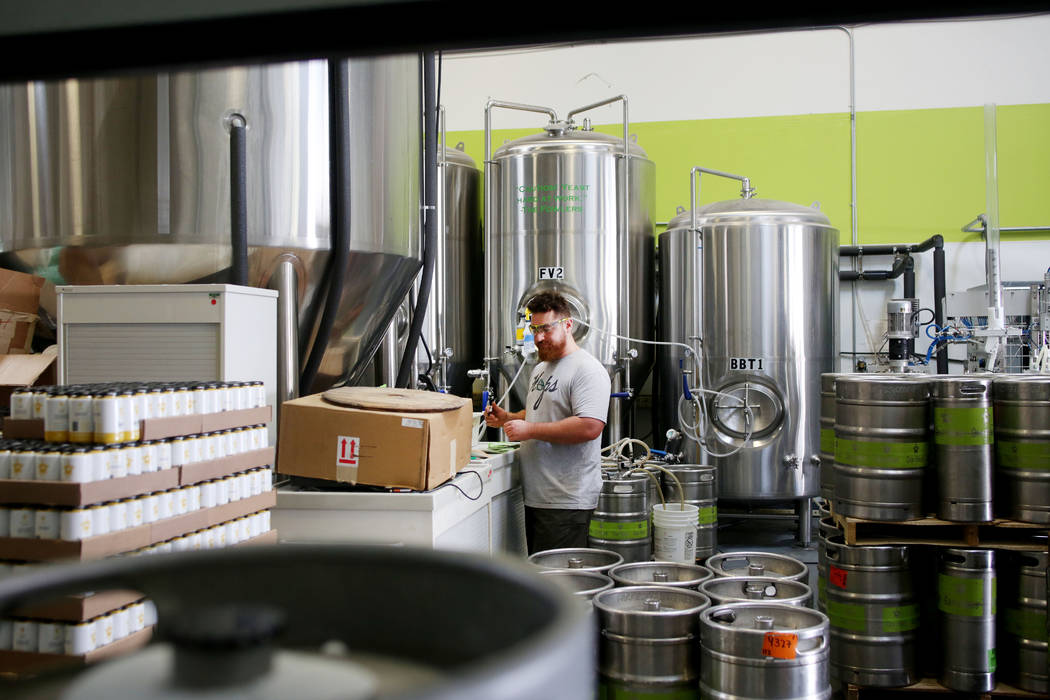 Assistant brewer Bryson Bauducco works on filling a keg order at CraftHaus Brewery in Henderson ...