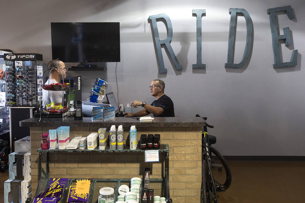 Joe Vara of Las Vegas purchases a repair on his bicycle from Pro Cyclery employee Shane Broussa ...