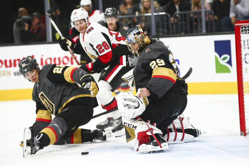 Golden Knights goaltender Marc-Andre Fleury (29) looks to stop the puck after losing his glove ...