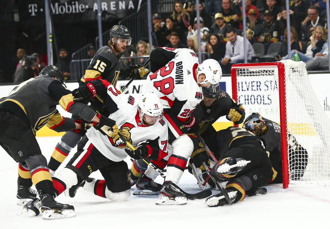 Ottawa Senators' Chris Tierney (71) and Connor Brown (28) try to get the puck in against the Go ...