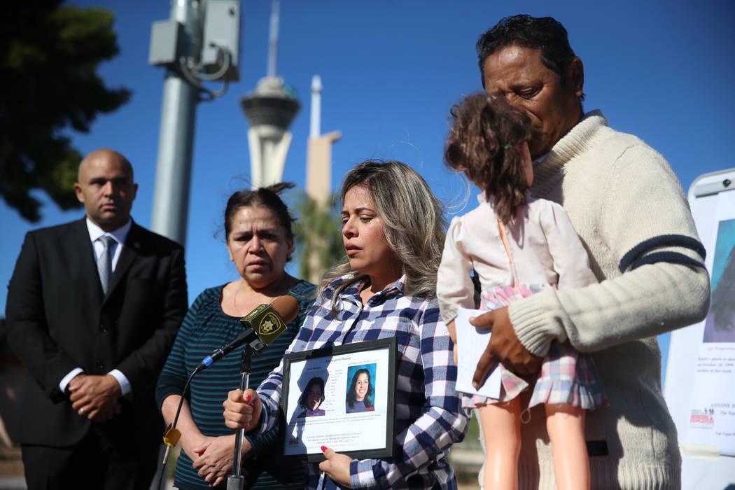 Las Vegas police Lt. Raymond Spencer, far left, listens to Rosy Rodriguez, center, with her par ...