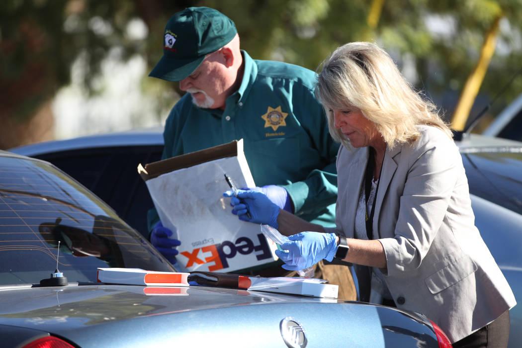 Las Vegas police homicide cold case investigators Dan Long, left, and Terri Miller collect DNA ...