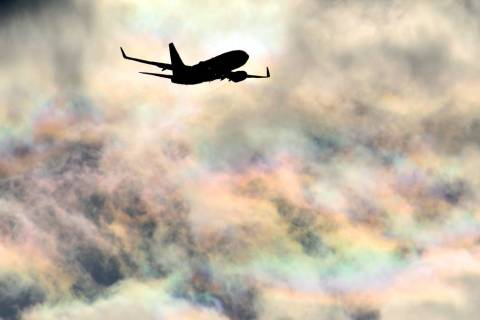 A Southwest Airlines plane flies under a rainbow sky as it approaches McCarran International Ai ...