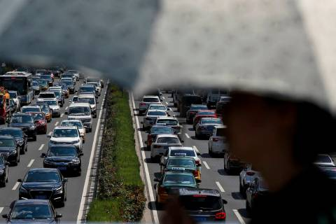 In an Aug. 13, 2019, file photo, a woman walks past vehicles on a city ring-road clogged with h ...
